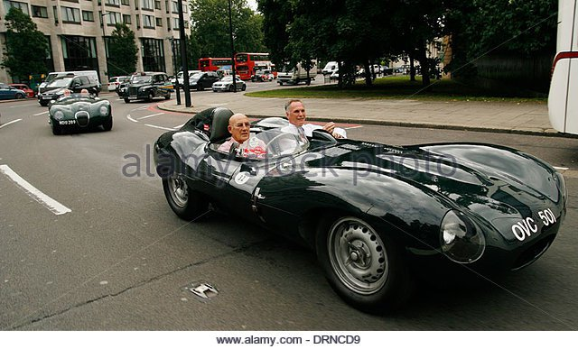 sir-stirling-moss-driving-a-jaguar-xk-around-hyde-park-corner-in-london-drncd9[1].jpg